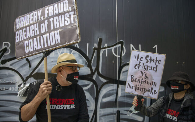 People protest against Prime Minister Benjamin Netanyahu hold banners outside his residence in Jerusalem,  May 24, 2020 (AP Photo/Ariel Schalit)