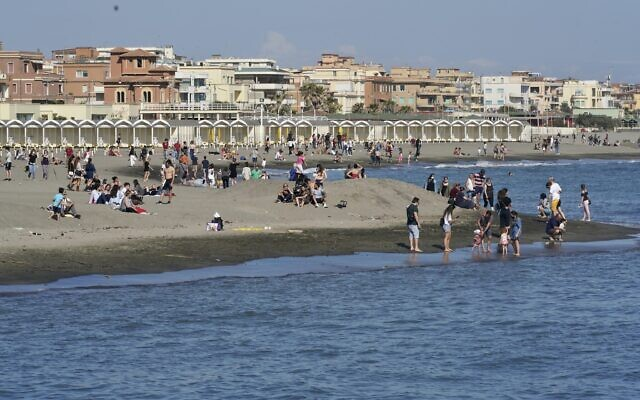 People enjoy the warm weather as they gather at Ostia beach, near Rome, Sunday, May 24, 2020. (AP Photo/Andrew Medichini)