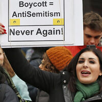 In this Jan. 19, 2019, file photo, political activist Laura Loomer holds up a sign across the street from a rally organized by Women's March NYC in New York (AP Photo/Kathy Willens, File)