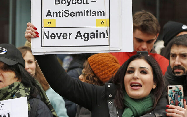 Far-right activist Laura Loomer holds up a sign emblazoned with the logo of Jewish terror group Kach, across the street from a rally organized by Women's March NYC, in New York on January 19, 2019. (AP/Kathy Willens)