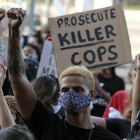 A demonstrator raises his fist during a protest of the death of George Floyd, a black man who died in police custody in Minneapolis, in downtown Los Angeles, May 27, 2020. (Ringo H.W. Chiu/AP)