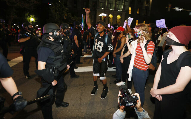 Denver police face off with protesters outside the State Capitol over the death of George Floyd, a handcuffed black man in police custody in Minneapolis, May 28, 2020, in Denver. (AP Photo/David Zalubowski)