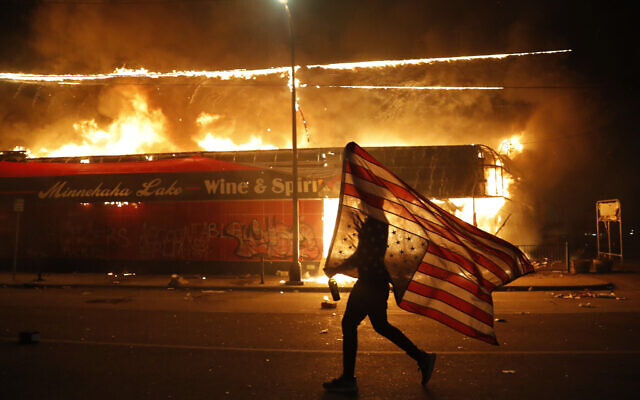 A protester carries a US flag upside down, a sign of distress, next to a burning building Thursday, May 28, 2020, in Minneapolis (AP Photo/Julio Cortez)