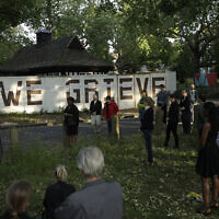 "Reverend William Taylor, top left, and local people standing with social distancing observe a 30 second silence during a remembrance event as they add the names of five people who recently died to the community ""We Grieve"" wall at Clapton Common, in London, May 28, 2020 (AP Photo/Matt Dunham)"