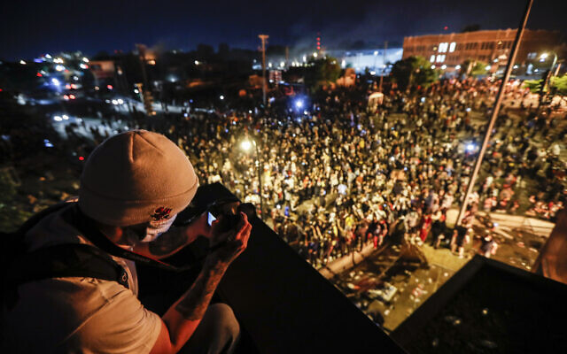 A protestor takes a picture of a demonstration from the roof of the Minneapolis 3rd Police Precinct, May 28, 2020, in Minneapolis. (AP Photo/John Minchillo)