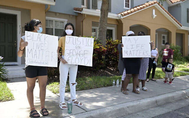 Protesters hold signs on a sidewalk across the street from a townhouse owned by Minneapolis police officer Derek Chauvin, May 29, 2020, in Windermere, Florida. (AP Photo/Phelan M. Ebenhack)