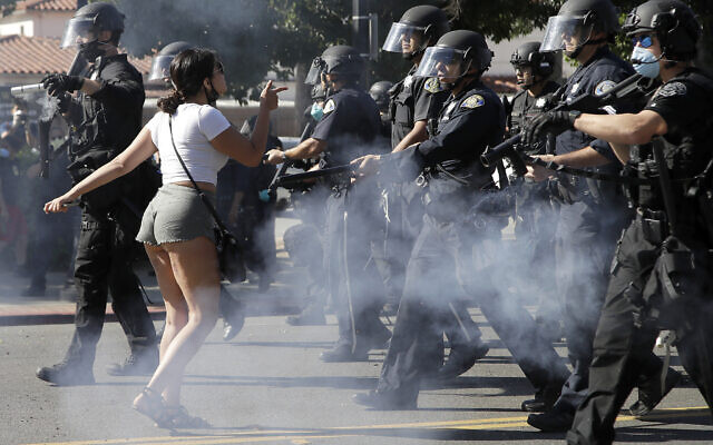 A protester confronts San Jose police as they advance on May 29, 2020, in San Jose, California as people demonstrate nationwide in response to George Floyd dying while in police custody on Memorial Day, in Minneapolis. (AP Photo/Ben Margot)