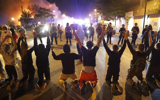 Demonstrators kneel before police, May 30, 2020, in Minneapolis (AP Photo/Julio Cortez)