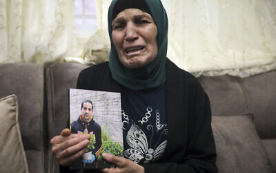 Rana, mother of Iyad Halak, 32, holds his photo at their home in East Jerusalem's Wadi Joz, May 30, 2020 (AP Photo/Mahmoud Illean)