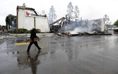 A man passes a burning bank building after a protest over the death of George Floyd, Sunday, May 31, 2020, in La Mesa, Calif. (AP/Gregory Bull)