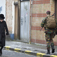 A Jewish boy walks past Belgian soldiers as they patrol during religious services in Antwerp, Belgium January 24, 2015. (AP Photo/Virginia Mayo)
