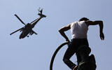 An Egyptian protester watches an Apache army helicopter is it flies over Tahrir Square, the focal point of Egyptian uprising, in Cairo Sunday, June 30, 2013.  (AP Photo/Amr Nabil)