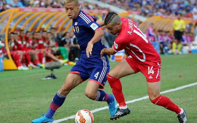 Japan's Keisuke Honda, left, and Palestine's Abdallah Jaber contest for the ball during the AFC Asia Cup soccer match between Japan and Palestine in Newcastle, Australia, January 12, 2014. (Rob Griffith/AP)
