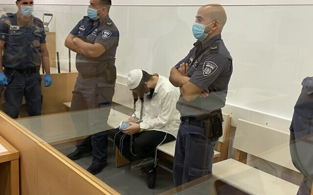 Amiram Ben-Uliel sits in the Lod District Court on May 18, 2020. (Jacob Magid/Times of Israel)