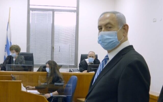 Prime Minister Benjamin Netanyahu at the start of his trial on corruption charges, May 24, 2020. Visible behind him are two of the three judges in the case, Rivka Friedman-Feldman and Oded Shaham (Screen capture/Government Press office)