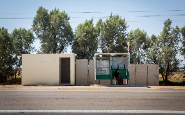 Illustrative: A woman waits at a bus stop near a public bomb shelter, by the southern kibbutz of Kfar Aza on July 06, 2015. (Miriam Alster/FLASH90)
