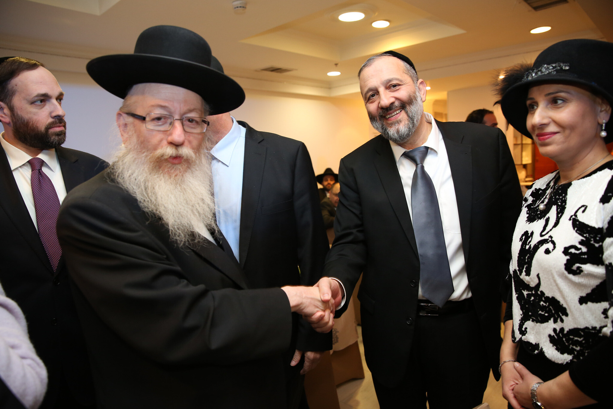 "Aryeh Deri, leader of the ultra-Orthodox Jewish Shas party, seen with United Torah Judaism's Yaakov Litzman at a ""Sheva Brachot"" event for Deri's daughter, soon after her marriage in Jerusalem, December 23, 2015. At right is Deri's wife Yaffa; at left is former Shas MK Ariel Atias (Yaacov Cohen/FLASH90)"