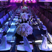 Tables at an event hall set out for a wedding. (Yaakov Naumi/Flash90)