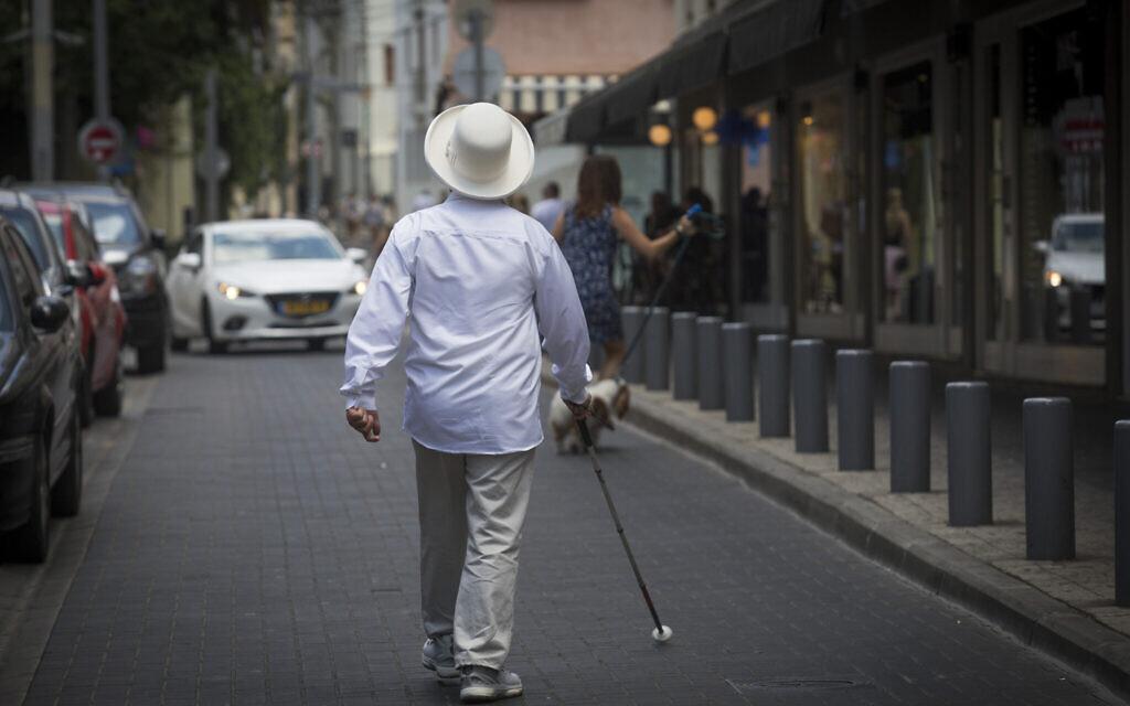Illustrative: A blind man walks in Tel Aviv on July 23, 2016. (Nati Shohat/Flash90)