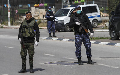Palestinian security forces guard at the entrance to the West Bank city of Nablus on March 23, 2020, as part of measures to contain the coronavirus. (Nasser Ishtayeh/Flash90)