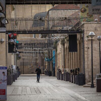 People walk past closed stores in the empty Mamilla Mall in Jerusalem, on March 23, 2020. (Nati Shohat/Flash90)