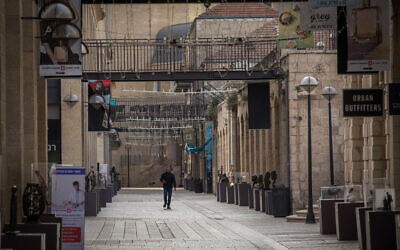 People walk past closed stores in the empty Mamilla Mall in Jerusalem, during a COVID-19 lockdown on March 23, 2020. (Nati Shohat/Flash90)
