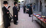 Ultra-Orthodox Jewish men pray outside a closed yeshiva in Bnei Brak on March 26, 2020. (Tomer Neuberg/Flash90)