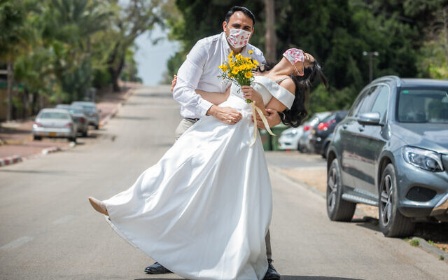 Illustrative: Gal Sade Knigsfild and Nofar Almakias pose for a picture with face masks before their wedding in Moshav Yashresh on April 6, 2020 (Yossi Aloni/Flash90)