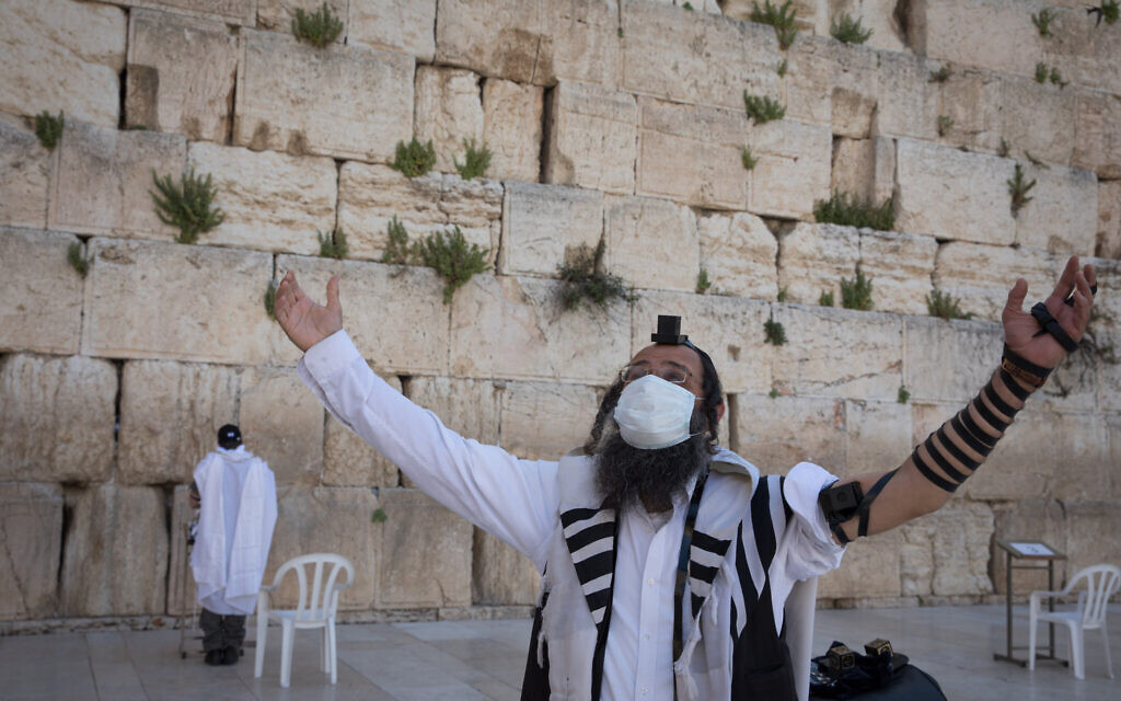 An ultra-Orthodox man, masked amid the COVID-19 crisis, gestures near the Western Wall in Jerusalem's Old City. April 19, 2020. (Nati Shohat/Flash90)