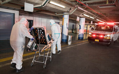Medical personel in protective gear bring a patient suspected of having the coronavirus to Shaare Zedek Medical Center in Jerusalem on April 30, 2020. (Nati Shohat/Flash90)