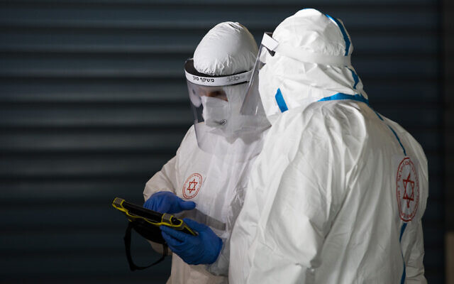 Magen David Adom workers wearing protective clothing seen outside the coronavirus unit at Shaare Zedek hospital in Jerusalem on April 30, 2020 (Nati Shohat/Flash90)