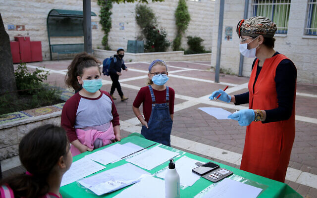 Israeli students at the Orot Etzion school in Efrat wear protective face masks as they return to school for the first time since the outbreak of the coronavirus, May 3, 2020. (Gershon Elinon/Flash90)