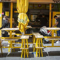 Israelis wearing face masks due to the coronavirus outbreak near a closed restaurant in Jerusalem, May 3, 2020. (Olivier Fitoussi/Flash90)
