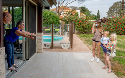 Grandparents receive a visit from their grandchildren in Kfar Yona on April 21, 2020 (Chen Leopold/Flash90)