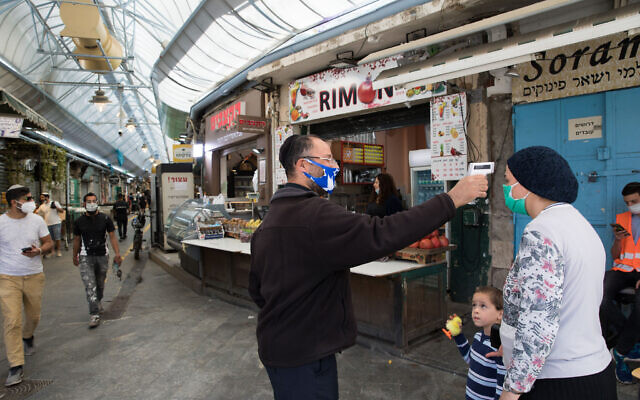 A man takes the temperature of a customer to check if she has a fever, at an entrance to the Mahane Yehuda market in Jerusalem, May 04, 2020. (Nati Shohat/Flash90)