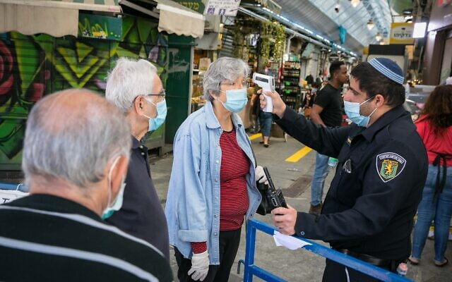 People have their temperature checked at they enter the Mahane Yehuda market in Jerusalem after it reopened according to the new government orders, May 7, 2020. (Olivier Fitoussi/Flash90)