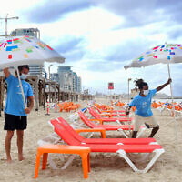 Workers arrange beach chairs and umbrellas at the Tel Aviv beach on May 5, 2020 (Avshalom Sassoni/Flash90)