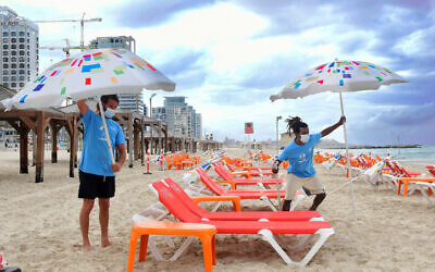 Workers arrange beach chairs and umbrellas at the Tel Aviv beach on May 5, 2020. (Avshalom Sassoni/Flash90)
