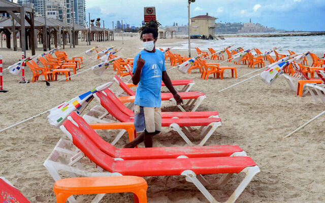 Workers arrange beach chairs and umbrellas at the Tel Aviv beach, May 5, 2020. (Avshalom Sassoni/Flash90)