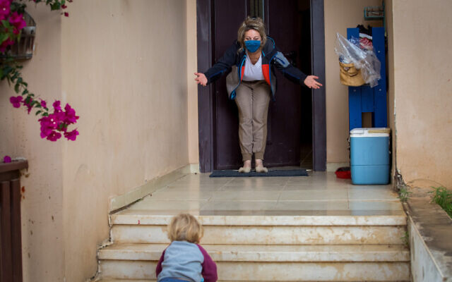 A boy visits his grandmother at her home in Moshav Haniel on April 5, 2020. (Chen Leopold/Flash90)