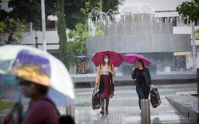 Israelis carry umbrellas on a rainy day in Tel Aviv. May 05, 2020. (Miriam Alster/FLASH90)