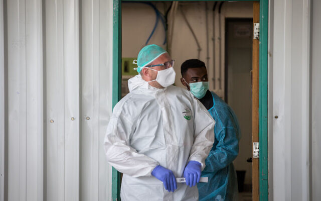 Medical workers wearing protective clothing as they stand outside the coronavirus unit at Shaare Zedek Medical Center in Jerusalem,  May 5, 2020. (Nati Shohat/Flash90)