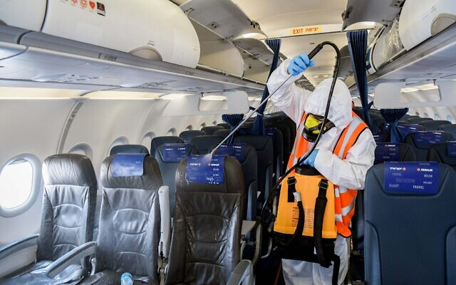 A worker wearing protective clothing disinfects andIsrair plane after its arrival from Moscow at the Ben Gurion International Airport, May 5, 2020. (Yossi Zeliger/Flash90)
