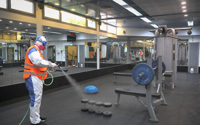 A worker wearing protective clothing disinfects a gym at the Tel Aviv University Sports Center, May 6, 2020. (Flash90)