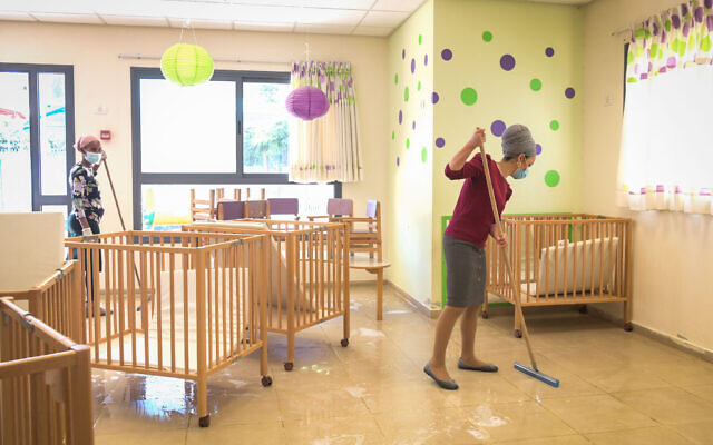 Staff clean a classroom at Emunah daycare in the city of Modiin, on May 7, 2020. (Yossi Zeliger/Flash90)