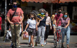 People wear protective face masks in Tel Aviv on May 8, 2020. (Miriam Alster/Flash90)