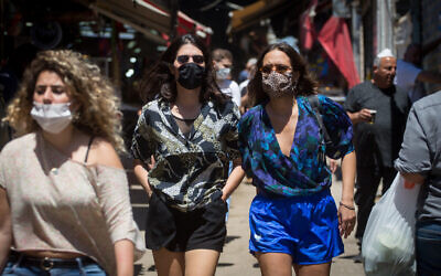People wear protective face masks as they shop at the Carmel market in Tel Aviv, on May 8, 2020. (Miriam Alster/FLASH90)