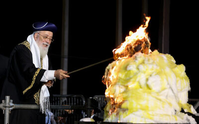 Sephardic Chief Rabbi of Jerusalem Rabbi Shlomo Amar lights a bonfire during the celebrations of the Jewish holiday of Lag B'Omer at Mount Meron in northern Israel on May 11, 2020. (David Cohen/Flash90)