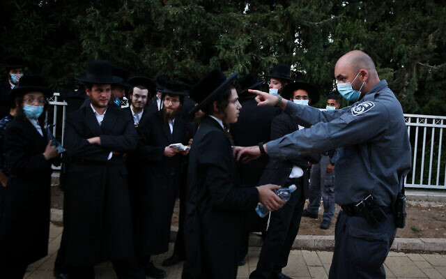 Ultra-Orthodox men clash with police officers during the celebrations of the Jewish holiday of Lag B'Omer on Mount Meron in northern Israel on May 12, 2020. (David Cohen/Flash90)