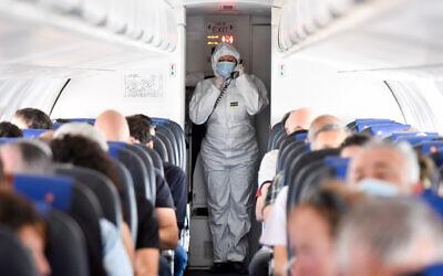 Illusrative: An Israir flight attendant wearing full protective gear walks next to passengers during an Israir flight between Tel Aviv and Eilat, May 13, 2020. (Yossi Zeliger/Flash90)